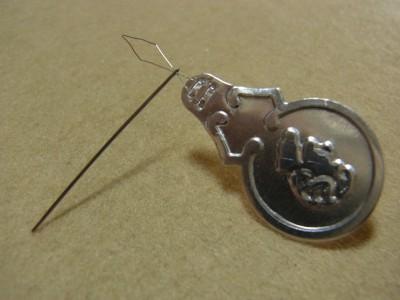 針穴に、針通し道具の先端部分をいれています。