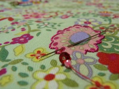 レーヨン糸で花の輪郭を細かくアウトラインステッチをします。次に、ピンクの花びら部分を中心に向けて、連続刺しをします。