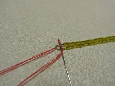 2列の竹ビーズの中心から針だし、上側の糸を中心から外側へ向かい下からすくって抜きます。