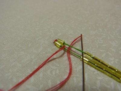 端の部分を束ねたら、両側の竹ビーズを、ひと粒下ろし図案線の中心から針を出します。同じ事を繰り返します。