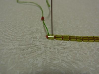 竹ビーズの上に短竹ビーズを刺します。束ねた竹ビーズの間から針を出し短竹ビーズをひと粒通し幅分で針を落とします。