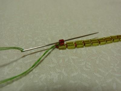 生地の下をくぐり、再び最初の糸部分に針を出し先程のビーズに通したら針を落とします。これを繰り返します。
