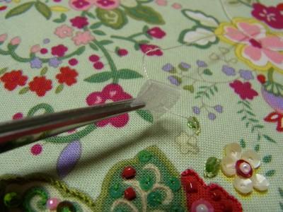 小花柄の生地から針を出し、三つ折りにした中心に糸を通します。
