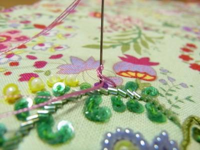 パイナップルのような花に、レーヨン糸を使い、ロングナッツステッチで4㎜カップ型スパンコールを止めます。※糸は4本どりで2回巻きです。