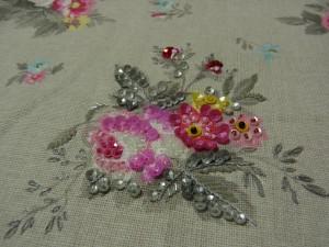 ピンクの薔薇と赤、黄色の小花に刺しています。ピンクの薔薇の花芯はスパンコールをロングナッツステッチで止めています。