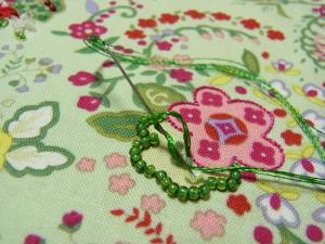 ピンクの花とグリーンの花の輪郭に刺繍をしています。グリーンの花の中心に3㎜スパンコールを刺しています。