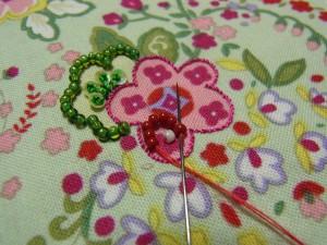ピンクの花の中にある、小花にビーズを刺しています。