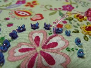 ピンクの花の縁取り部分を、レーヨン糸4本どでアウトラインステッチをしています。