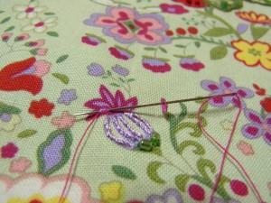 パイナップルの花模様にレーヨン糸(パープル)2本どりで、縦模様にアウトラインステッチをします。下部に竹ビーズを、ひと粒刺しします。上部に4㎜カップ型スパンコールを刺します。刺し方です。スパンコールを山側から通し、半径分の生地をすくったら最初の糸が出ている部分に針を出します。
