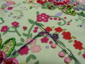紫の小花を刺します。刺し方です。丸小ビーズ3粒を一度に通し、最初のひと粒目にだけに針を通し、そのまま抜きます。