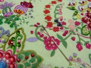 ピンクの花の輪郭を、レーヨン糸2本どりでボタンホールステッチをします。周りの小花はポリエステル糸1本どりでナッツステッチをします(2回巻き)です。