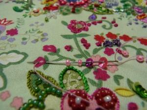 先程のピンクの花の中は、丸小ビーズのひと粒刺しと3㎜カップ型スパンコールを丸小ビーズで止めています。手前に三角形の形をした花があります。こちらの花は、4㎜、3㎜カップ型スパンコール、丸小ビーズ2粒を一度に通し最初の糸が出ている部分に戻し、そのまま抜きます。