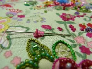 進行方向に戻す為、再びスパンコールとビーズの穴に針を戻し糸を締めます。針を、ビーズの際の糸が出ている部分に戻し裏で玉止めをします。