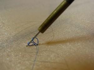 最初の糸が出ている部分から1㎜ほど先に針を落とし、もう一方の手で、針先に糸を掛けます。糸が外れないように注意し、針を180°回転させながら引き揚げます。生地の上には最初の糸と2回目に引き上げた糸の2本があります。
