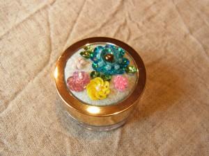 体験用のアクリルケースです。ブルー、ピンク、黄色、白の花が刺繍されています。