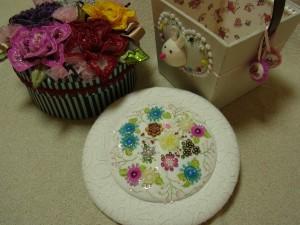 手前は、花模様の壁掛け。 右後ろは可愛いウサギの小物入れ。 その隣は、お花畑の丸箱です。