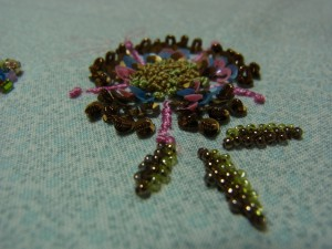 2色(淡いグリーンと、茶色)の糸を使い、花の中心を刺しています。手前の葉が完成しています。もう一方の葉を刺したら花の部分は完成です。密に刺してあるからモリモリで可愛い!