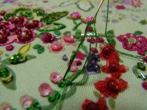 オーガンジーで作った花と、3㎜カップ型スパンコールの小花があります。その下にレーヨン糸でナッツステッチをしています。