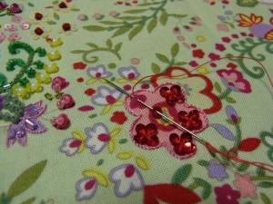 ピンクの花の縁取りの刺繍が終わっています。4㎜カップ型スパンコールを使って花の中の小花を刺しています。
