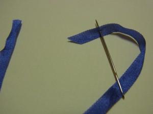リボンの先端を斜めにカットし針穴に通します。先端より2~3㎝入った位置に針を入れて抜きます。