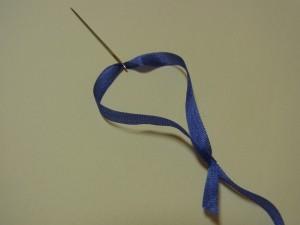 針を抜ききった状態です。ここから、縮めていきます。リボンが交差している部分(最初に、針を通した箇所)を手で押さえ長いほうのリボンを、ゆっくり手前に引きます。