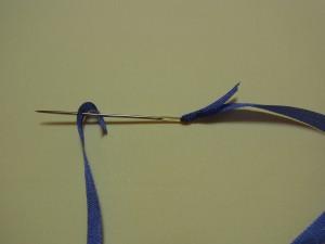 長いほうのリボンの先端を、1㎝程折ります。その部分に針を刺し引き抜きます。