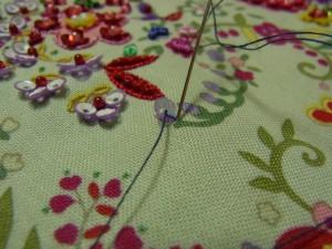 スパンコールの際の糸部分に針を落として、糸がゆるまないように締めます。