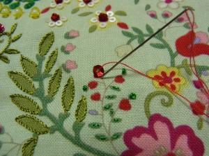 スパンコールの際の糸部分に針を落とします。糸がゆるまないように、きちんと締めます。