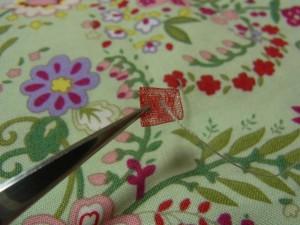 花模様の中心から針を出し、三つ折りにしたオーガンジーリボンの中心に糸を通します。