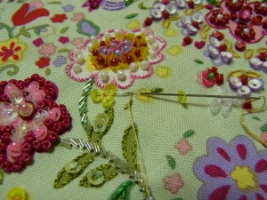 黄色の小花を刺します。スパンコールを山側から通し、半径分(スパンコール)の生地をすくって最初の糸部分に戻ります。※花の中心に向かって刺します。