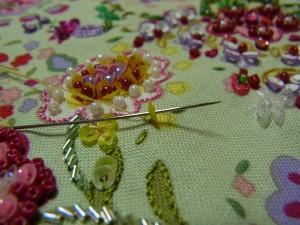 糸を抜いて再びスパンコールの穴に通し、スパンコールの際の糸部分に針を落とします。これを繰り返し3枚の花びらを作ります。左に完成した花びらがあります。