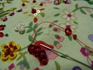 赤いチュウーリップの花に刺します。4㎜カップ型スパンコールを山側から通し、続けてビーズを通します。半径分(スパンコール)の生地をすくって最初の糸部分に戻ります。