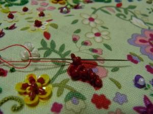 糸を抜いて再びスパンコールの穴に針を戻し、次のスパンコールとビーズを一緒に通します。これを繰り返します。