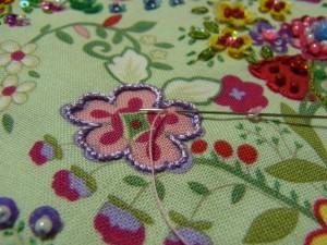 ピンクの花の輪郭はアウトラインステッチで刺してあります。花の中は4㎜カップ型スパンコールを山側から通し、半径分(スパンコール)の生地をすくって最初の糸部分に針を戻します。