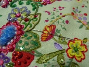 横を向いている花に、ブリオンローズステッチを刺繍します。ポリエステル糸の2本どりです。向こう側から針を出し、手前に入れて再び最初の糸部分に針を出します。