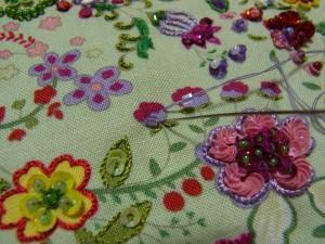 濃いピンクの花を刺します。向う側から針を出し、短竹ビーズを通しビーズの幅で手前に針を落とします。ハノ字の逆になるように刺します。