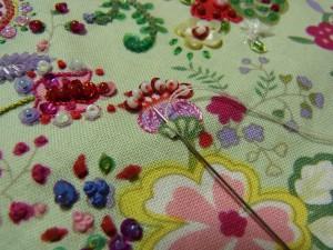 パイナップル模様の花に刺しています。ポリエステル糸の2本どりです。向う側から針を出し手前に入れて、再び最初の糸部分に針を戻します。
