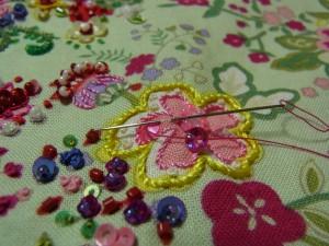 次のスパンコールを通します。生地を半径分すくって1枚目のスパンコールの際の糸部分に針をもどします。同じことを繰り返します。