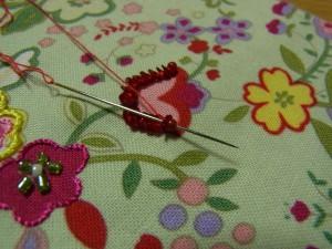 赤い縁取りのチューリップのような花に刺しています。スパンコールを山側から通し、続けてビーズを通します。刺す手順は③と同じです