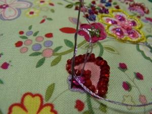 チュウリップのような花の上部を刺しています。4㎜カップ型スパンコールの穴から針を出し、糸を時計方向に2回巻いたら針を生地に落とします※レーヨン糸2本どりです