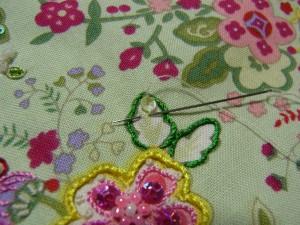 黄色い花の横にある葉に刺します。途中までは③と同じです。再び穴から針を出し、スパンコールの際の糸部分に針を戻します。横方向に刺していきます。