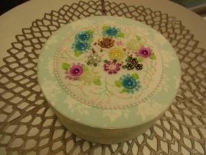 凄~~い!! 課題である、壁掛け(flower)が丸箱に変身です!!ピンク、ブルー、黄色、シルバーな花が刺してあり、その周りにパールが刺してあります。箱本体の生地が淡いブルーなので、とても爽やかです。