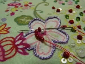 紫色の花の中にビーズをひと粒刺します。そのビーズを取り囲むように、ビーズを6粒通し最初の1つ目に針を通します。