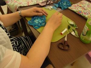 青い花のチャームは刺繍が終わりました。3枚の花びらと葉を組み立てています。