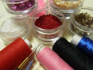 スパンコール、ビーズ、糸、アリワークの針などが並んでいます。