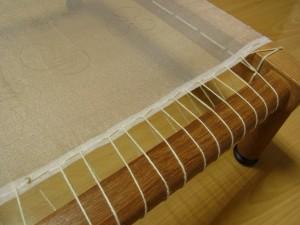 縦棒にタコ糸1本どりで生地を張っています。並縫い部分に糸を掛けています