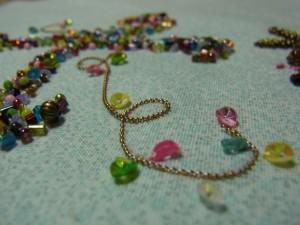 ワイヤを茎のように這わせて、コーチングします。次に、ピンク、黄色、ブルー、グリーン、白の4㎜カップ型スパンコールを、ワイヤーの両端に片止めします。