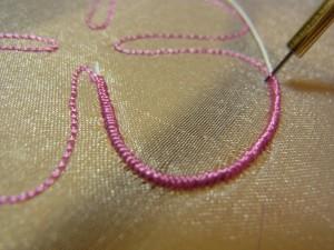 ピンクの花の輪郭にワイヤーを入れながら刺しています。