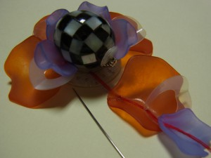 金具に生地を被せて、シェルを縫い止めます。次に樹脂の花びらオレンジ→ドーナツ型のスパンコール(半分に折る)→紫の順番で通して、縫いとめていきます。