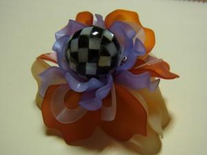 オレンジの花びらの外側に、ベージュの樹脂の花びらを刺していきます。